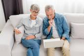 érett férfi és nő nézi laptop új házban