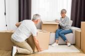 zralé muž držení box a žena sedí na pohovce v novém domě