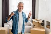 usmívající se muž držící klíče a ukazující prstem v novém domě