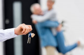 selective focus of broker holding keys of new house and couple on background