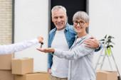 oříznutý pohled makléře dávat klíče od nového domu na usmívající se muž a žena