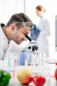 Photo selective focus of smiling molecular nutritionist using microscope in lab