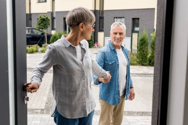 woman holding hands with man and entering to new house