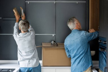 back view of mature man opening door and woman arranging books in new house