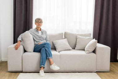 Mature woman in glasses sitting on sofa in new house stock vector
