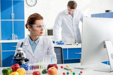 Selective focus of molecular nutritionist looking at computer and colleague on background stock vector