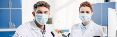 panoramic shot of molecular nutritionists in medical masks looking at camera