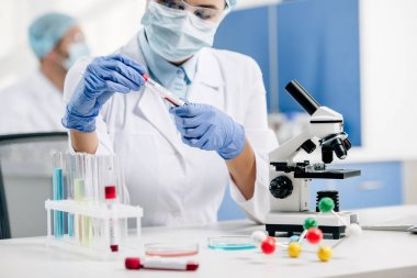 cropped view of genetic consultant in white coat doing dna test in lab