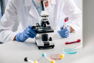 cropped view of genetic consultant using microscope and holding test tubes
