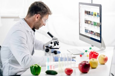 KYIV, UKRAINE - OCTOBER 4, 2019: side view of molecular nutritionist using computer with youtube website stock vector