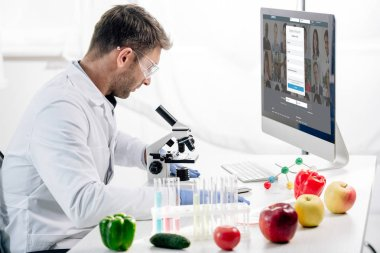 KYIV, UKRAINE - OCTOBER 4, 2019: side view of molecular nutritionist using computer with linkedin website stock vector