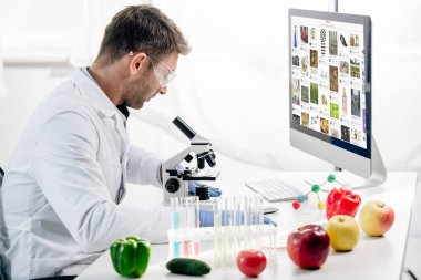 KYIV, UKRAINE - OCTOBER 4, 2019: side view of molecular nutritionist using computer with pinterest website stock vector