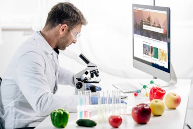 KYIV, UKRAINE - OCTOBER 4, 2019: side view of molecular nutritionist using computer with shutterstock website stock vector