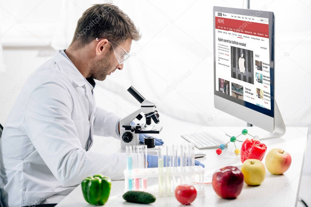 KYIV, UKRAINE - OCTOBER 4, 2019: side view of molecular nutritionist using computer with bbc website stock vector