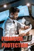 bi-rasový obchodník pomocí kalkulačky a držení grafů a grafů v blízkosti písmen finanční ochrany