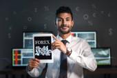 šťastný bi-rasový obchodník držící digitální tablet s forexovými písmeny