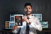 šťastný bi-rasový obchodník držící digitální tablet s písmeny finanční ochrany