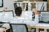 Rückseite des Händlers, der Ja-Geste zeigt und in der Nähe von Computern sitzt, mit Grafiken in der Nähe von Geldzeichen