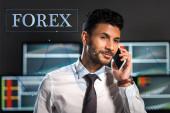 boldog bi-rasszista kereskedő beszél okostelefon közelében forex betűk