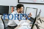 Photo happy bi-racial trader showing yes gesture near forex letters