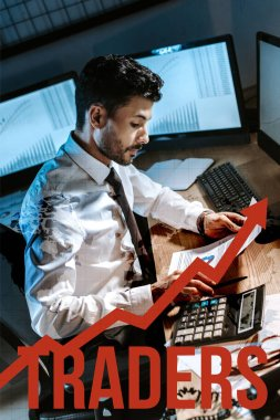 bi-racial man using calculator and holding charts and graphs near traders letters