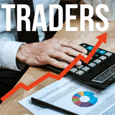 cropped view of man using calculator near traders letters