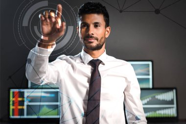 Selective focus of handsome bi-racial trader pointing with finger near computers on background stock vector