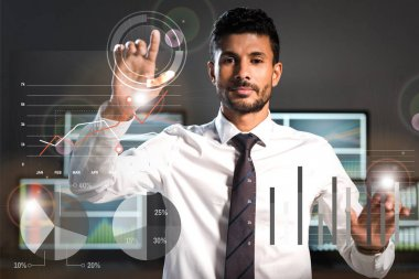 Selective focus of handsome bi-racial trader pointing with fingers near computers on background stock vector