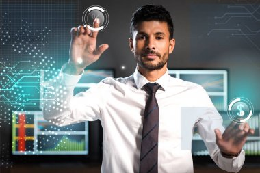 Selective focus of handsome bi-racial trader pointing with fingers near computers stock vector
