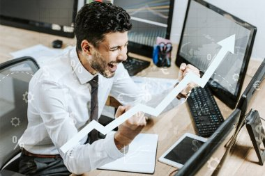Happy bi-racial trader showing yes gesture near computers and raising graphs stock vector