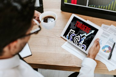 selective focus of man holding cup and digital tablet with traders letters