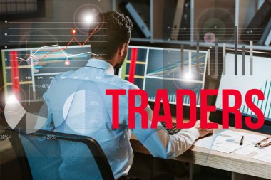 back view of man working near computer with graphs and traders letters