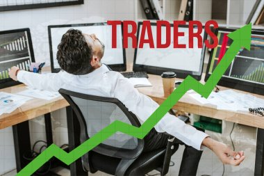 bi-racial man with outstretched hands sitting near computers and traders letters