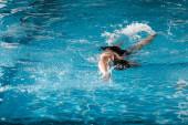 atletický muž potápění v bazénu s modrou vodou