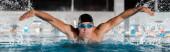 Panoramaaufnahme einer schönen Schwimmerin, die Schmetterlingsschlag im Schwimmbad schwimmt