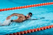 Fotografie kapky vody v blízkosti plavce s otevřenými ústy trénink v bazénu