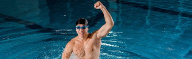panoramic shot of excited swimmer in goggles celebrating triumph