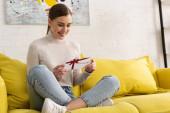 Usmívající se mladá žena s dárkovým poukazem na pohovce v obývacím pokoji