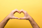 cropped view of man showing heart gesture on yellow background