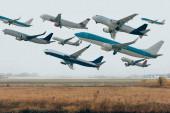 Letadla na zatažené obloze nad travnatým letištěm