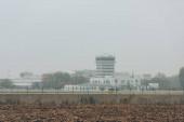 Fotografie Letiště s přistávací dráhou a letištními budovami s oblačným nebem na pozadí