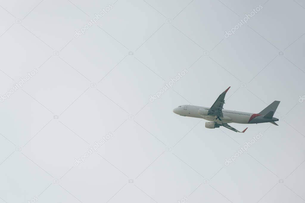 Low angle view of commercial jet plane in cloudy sky stock vector