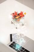 Selektivní zaměření hraček dárky v košíku vedle notebooku a kreditní karty a ilustrace