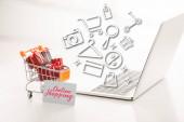 Dětský vozík s dárkovými krabicemi vedle kreditní karty a notebooku na bílém povrchu, online nákupní koncept