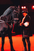 Kijev, Ukrajna - 2019. november 1.: Side view of handler performing with horse at circus stage