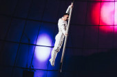 KYIV, UKRAINE - NOVEMBER 1, 2019: Gymnast performing exercise with pole in circus