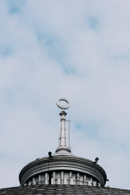Low angle view of spire with circle on building with cloudy sky at background