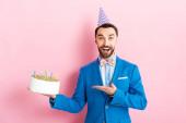 vzrušený podnikatel ve straně čepice ukazující rukou na narozeninový dort na růžové