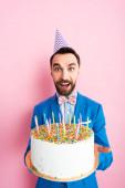 šťastný podnikatel ve straně čepice drží narozeninový dort se svíčkami na růžové