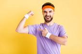 aufgeregter Mann zeigt mit dem Finger auf Muskel isoliert auf gelb